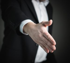 A man extending his hand to offer a handshake