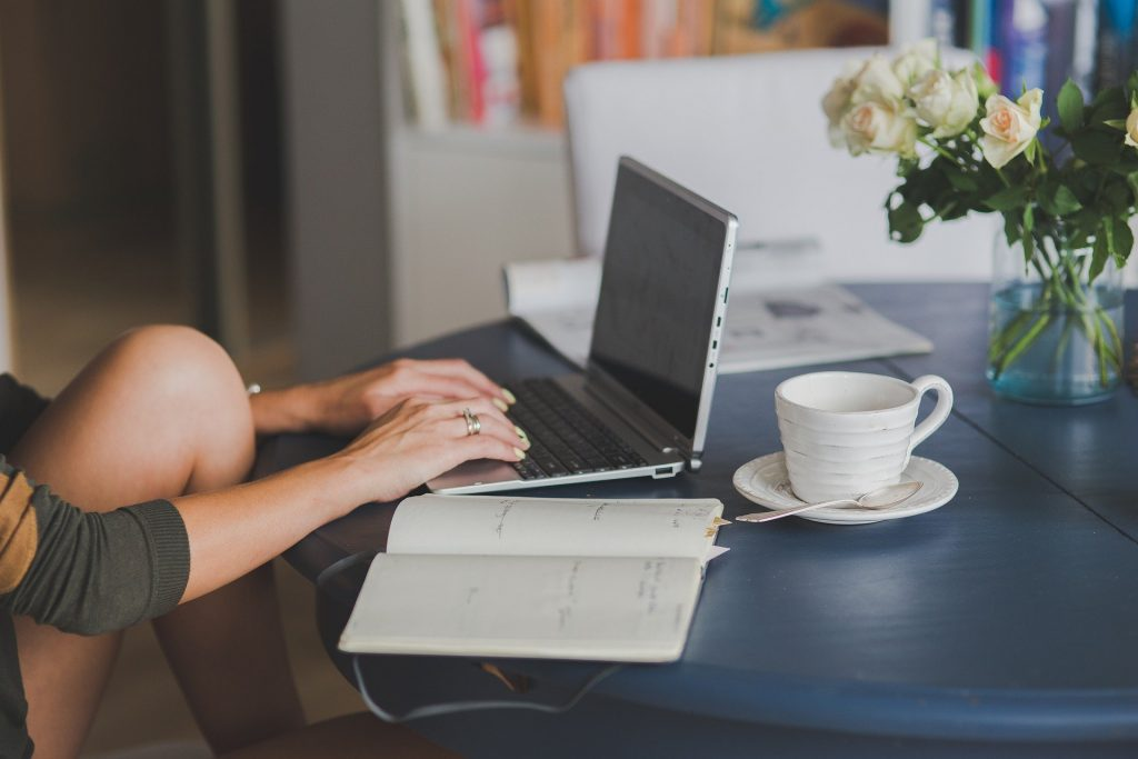 An image of a woman typing on a laptop.